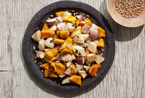 A picture of Roasted Turnips and Winter Squash With Agave Glaze from directly above. The orange and pale root vegetables sit on a slate grey plate with a brown bowl full of a darker brown grain sit in the upper right hand corner of the image.