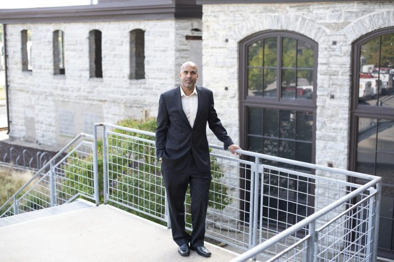 Damien Fair, one of the MacArthur Fellowship grant winners, standing on an outdoor staircase landing with stone buildings in the background, wearing a black suit with a white shirt, and no tie.