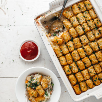Chicken Pot Pie Tater Tot Hot Dish, with a spoonful taken out of the dish and some put into a bowl, and a separate Bowl of Ketchup